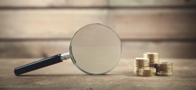 Szkło powiększające i monety na drewnianym stole.