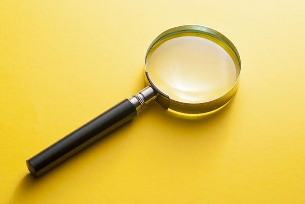 Szkło powiększające leżące po przekątnej na żółto
