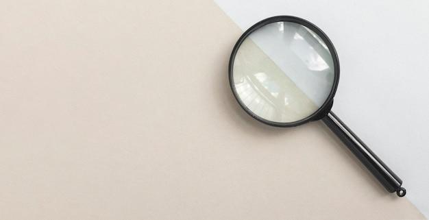 Szkło powiększające lub lupa na jasnoniebieskim i beżowym banerze lupy z miejscem na kopię