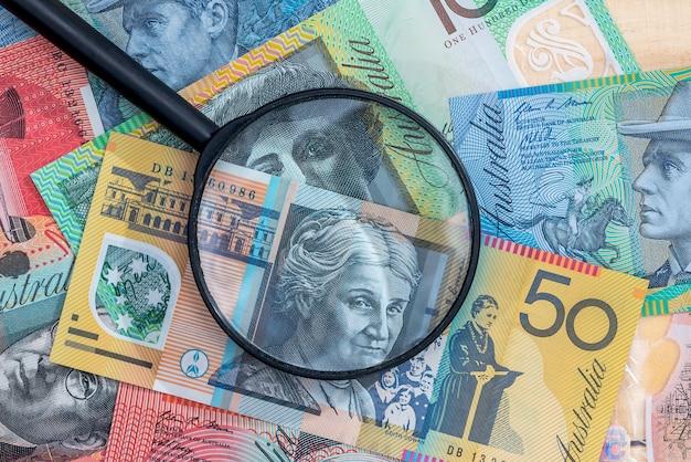 Szkło powiększające na banknot dolar australijski jako tło