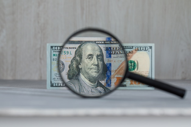 Szkło powiększające na banknot dolara na szary i drewniany stół