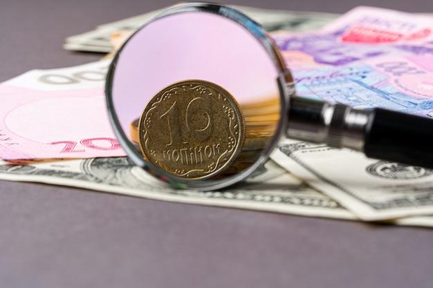 Szkło powiększające na banknotach hrywny ukraińskiej i dolarach amerykańskich. koncepcja kursu walutowego