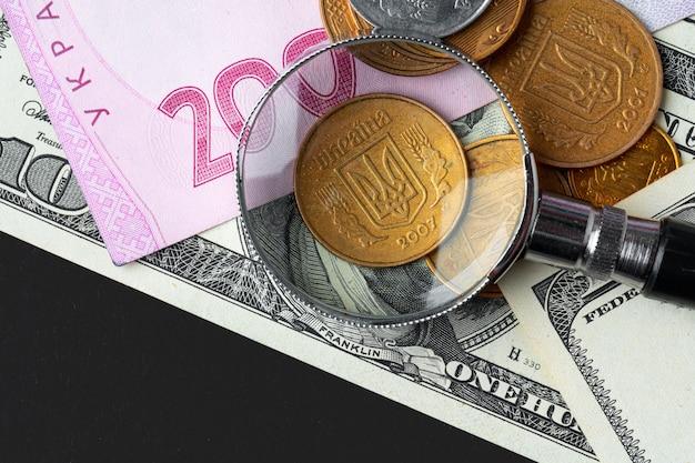 Szkło powiększające na banknotach hrywny ukraińskiej i dolarach amerykańskich