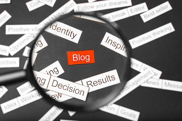 Szkło powiększające na czerwonym blogu z wycięciem z papieru