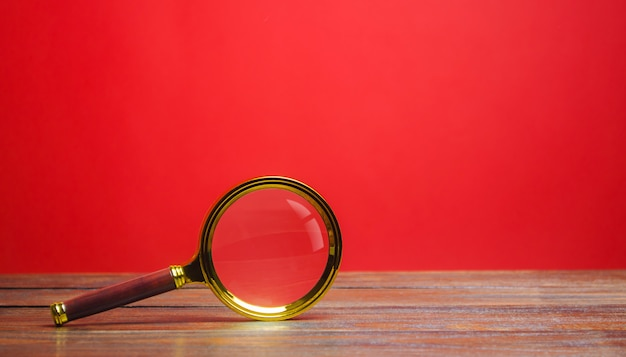 Szkło powiększające na czerwonym tle. wyszukiwanie i analiza, analizy i badania.