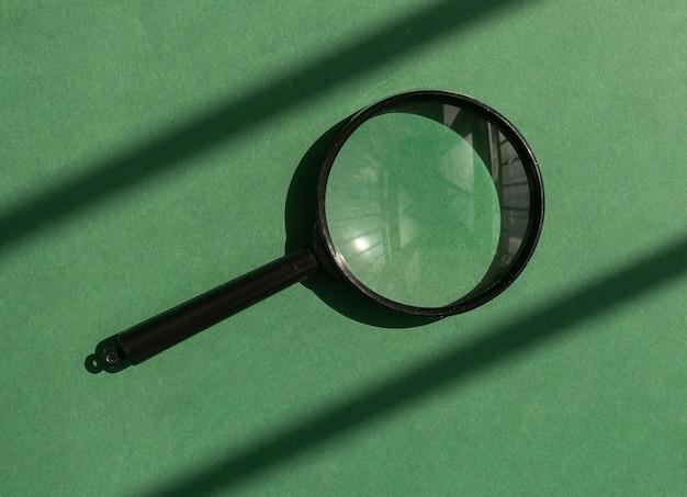 Szkło powiększające na eko zielonym tle ze słonecznym światłem lupy jako koncepcja qna