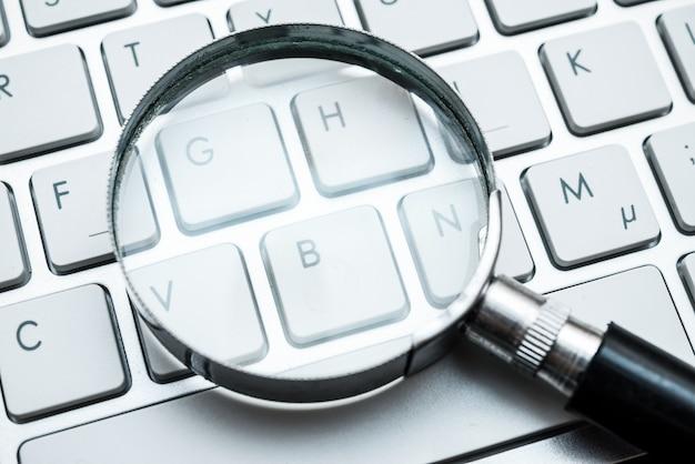 Szkło powiększające na klawiaturze komputera. internetowa koncepcja wyszukiwania i słów kluczowych