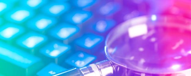 Szkło powiększające na klawiaturze laptopa w świetle neonowym.