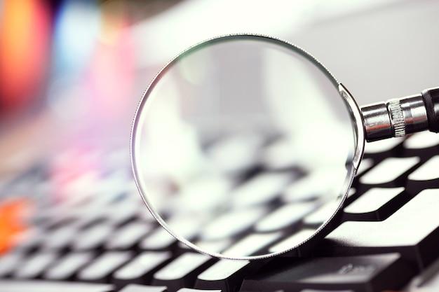 Szkło powiększające na klawiszach czarnej klawiatury komputera.