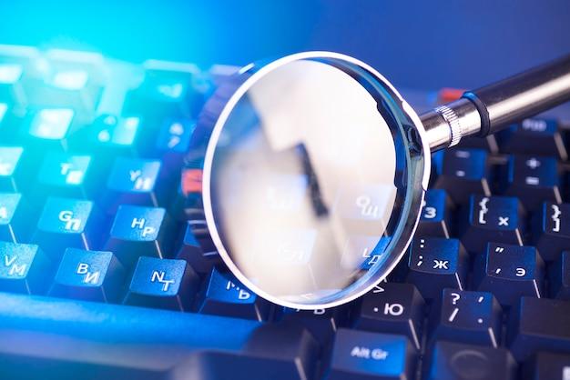 Szkło Powiększające Na Klawiszach Czarnej Klawiatury Komputera. Premium Zdjęcia