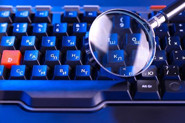 Szkło powiększające na klawiszach czarnej klawiatury komputerowej.