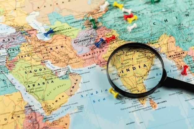 Szkło powiększające na mapie świata selektywne focus w indiach. - koncepcja ekonomiczna i biznesowa.