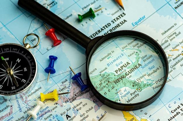 Szkło powiększające na mapie świata selektywne fokus na mapie papui-nowej gwinei. - koncepcja podróży i biznesu.