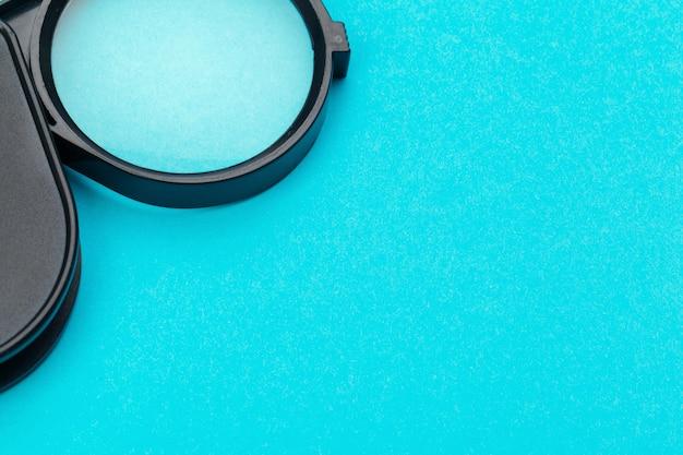 Szkło powiększające na niebieskim pastelowym kolorze.