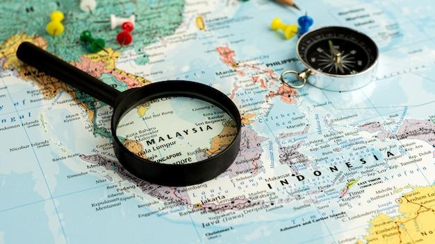 Szkło powiększające na selektywnej mapie świata na mapie malezji. - koncepcja ekonomiczna i biznesowa.