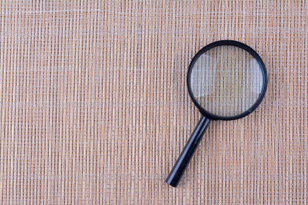 Szkło powiększające na tle drewna, symbol wyszukiwania