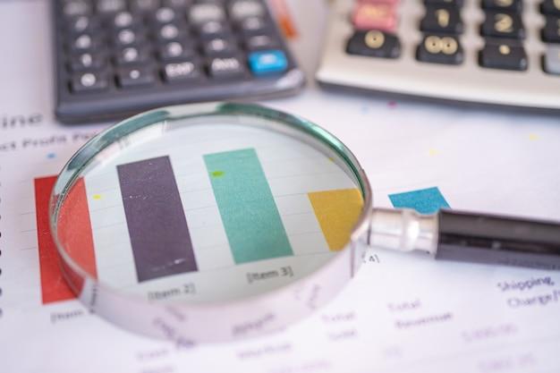 Szkło Powiększające Na Wykresach Papieru Wykresów Premium Zdjęcia