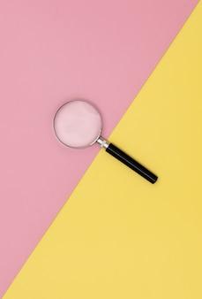 Szkło powiększające na żółtym i różowym tle.