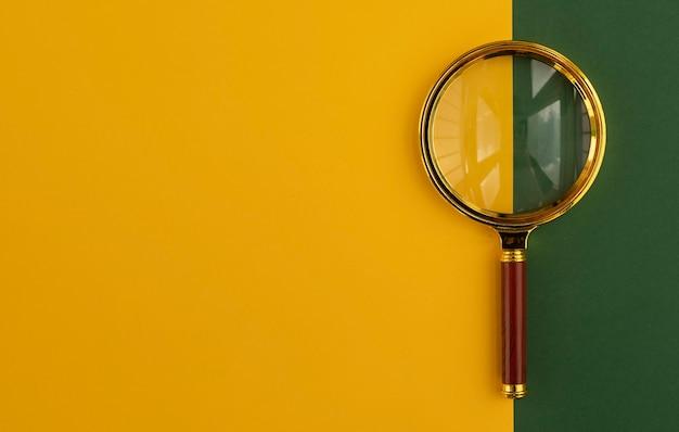 Szkło powiększające na żółtym i zielonym tle