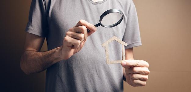 Szkło powiększające patrzy na dom. wyszukiwanie nieruchomości na brązowym tle