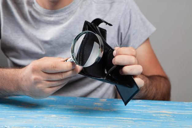 Szkło powiększające patrzy na pusty portfel