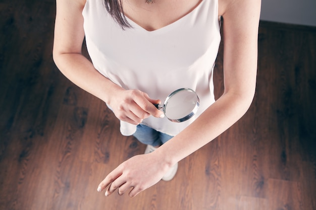 Szkło powiększające patrzy na rękę. badanie ciała