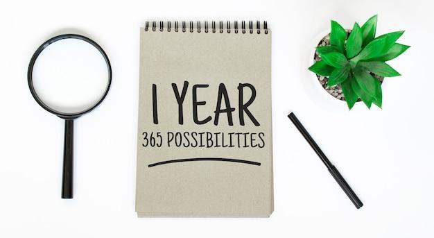 Szkło powiększające, pusty brązowy notatnik na białym stole. 1 rok 365 możliwości znak