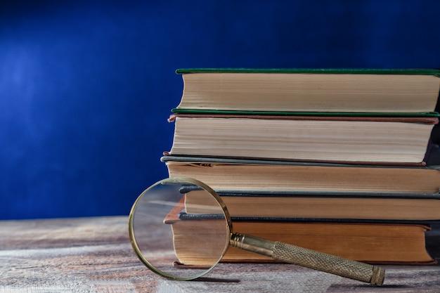 Szkło powiększające w pobliżu starych książek na ciemnoniebieskim