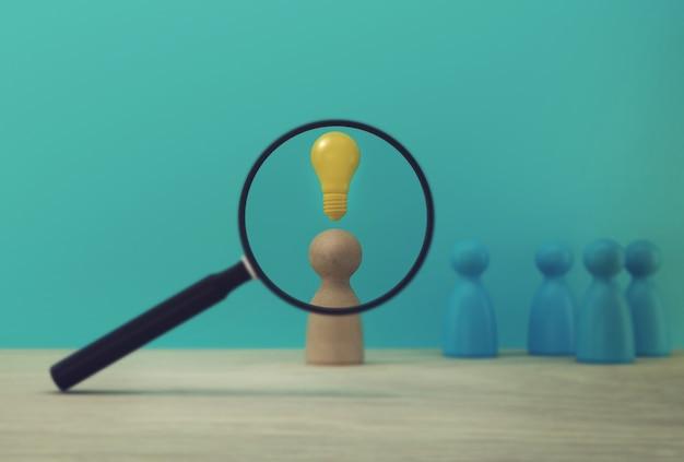 Szkło powiększające z modelami ludzi i ikoną żarówki wyróżniającymi się z tłumu. zespół zarządzania zasobami ludzkimi i talentami oraz budowania biznesu pracownika w organizacji