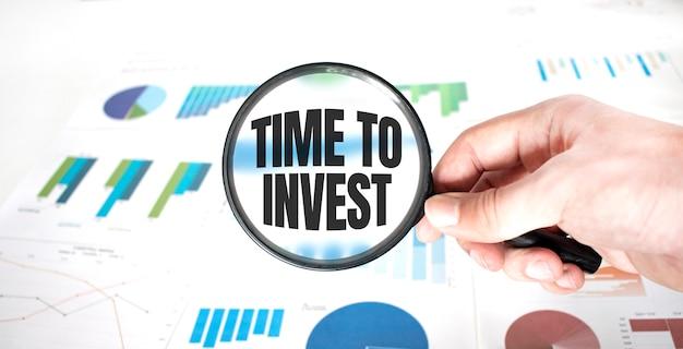 Szkło powiększające z napisem czas na inwestycje nad drewnianym
