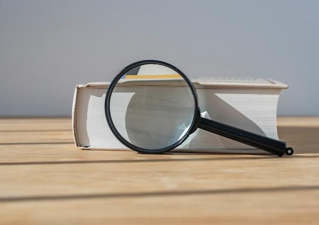 Szkło powiększające z zamkniętą grubą książką na drewnianym stole ze światłem dziennym