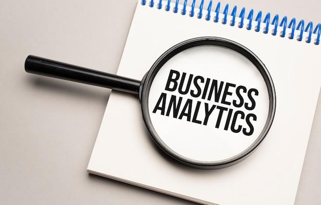 Szkło powiększające ze słowem analityka biznesowa na tle wykresu