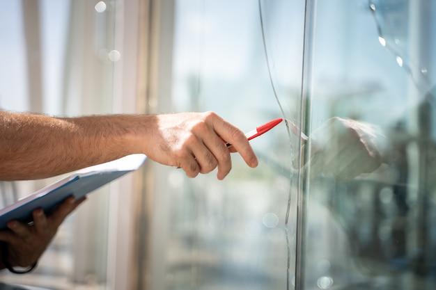 Szkło rozbite z domu przez wypadek, człowiek sprawdza, czy do naprawy