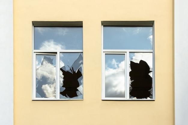 Szkło rozbitych okien odbija niebo, dom z rozbitymi oknami z bliska.