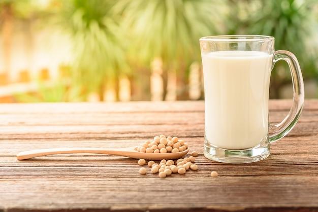 Szkło soi mleko z soją na drewnianym stole i plamy tle