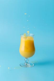 Szkło sok pomarańczowy i błękitny tło