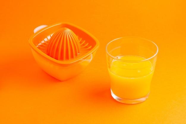 Szkło sok pomarańczowy i sokowirówka na pomarańczowym tle
