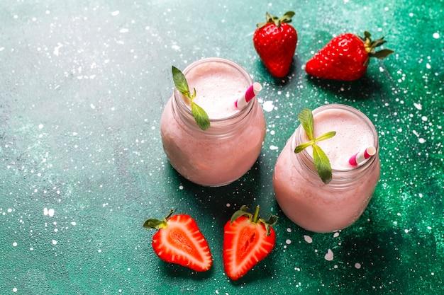 Szkło świeży truskawkowy milkshake, smoothie i świeże truskawki, zdrowy jedzenie i napój pojęcie.