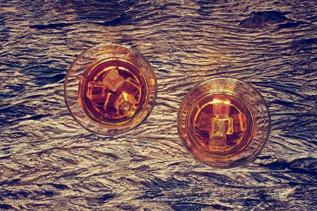 Szkło whisky bourbon z lodem na drewnianym tekstury tle.