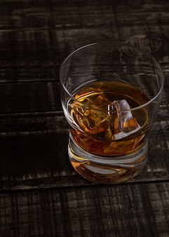 Szkło whisky z kostkami lodu na drewnianego stołowego tła odgórnym widoku