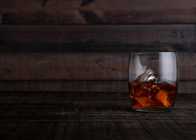 Szkło whisky z kostkami lodu na drewnianym stołowym tle