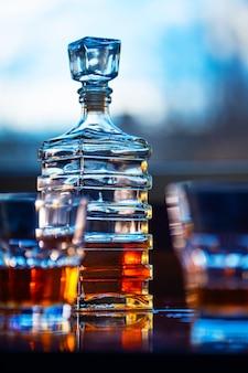 Szkło whisky z starą kwadratową karafką na drewnianym stole
