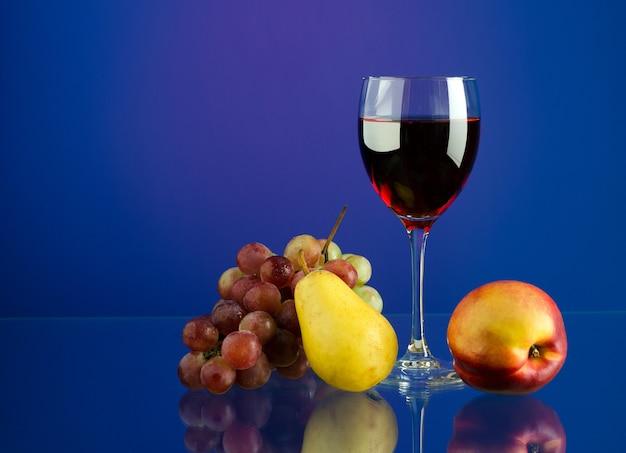 Szkło z czerwonego wina, pędzel winogron i owoców na jasnym tle wielokolorowe z odbiciem z miejsca kopiowania tekstu.