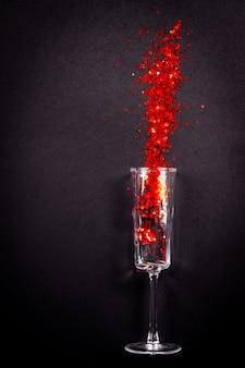 Szkło z czerwonym brokatem na czarnym, wakacyjnym płasko ułożonym