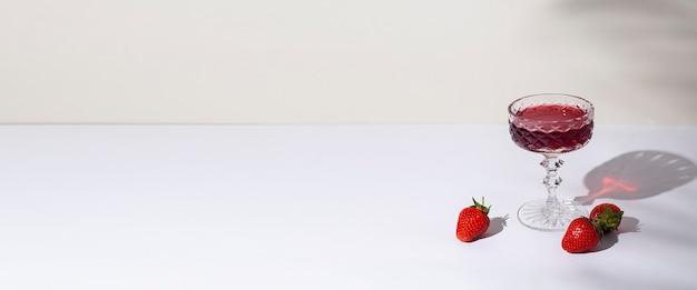 Szkło z czerwonym winem i truskawkami na stole na jasnym tle. widok z góry, układ płaski. transparent.