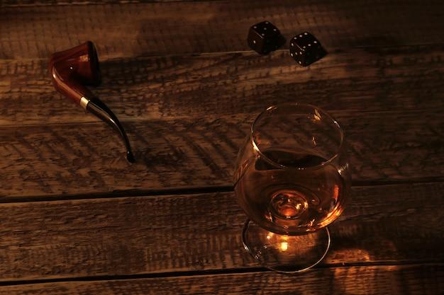 Szkło z koniakiem, kostką i fajką na drewnianym stole