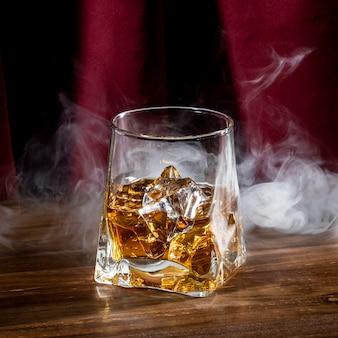 Szkło z kostką lodu i dymem