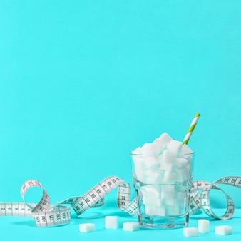 Szkło z kostkami cukru i miarką. kontrola wagi, dieta i koncepcja detoksykacji niebieskie tło