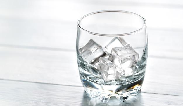 Szkło z kostkami lodu na drewnianym stole