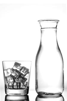 Szkło z lodem i butelką woda na białym tle.